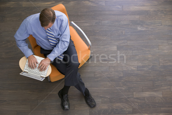 Businessman sitting indoors with laptop Stock photo © monkey_business