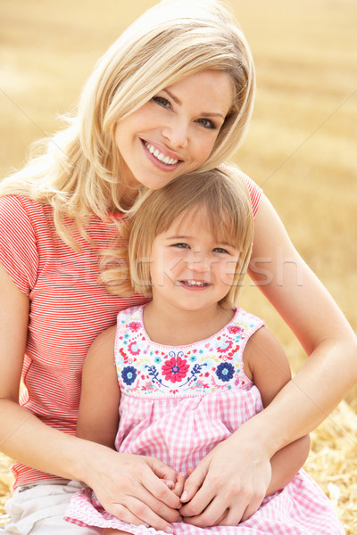 Mother And Daughter Sitting On Straw Bales In Harvested Field Stock photo © monkey_business