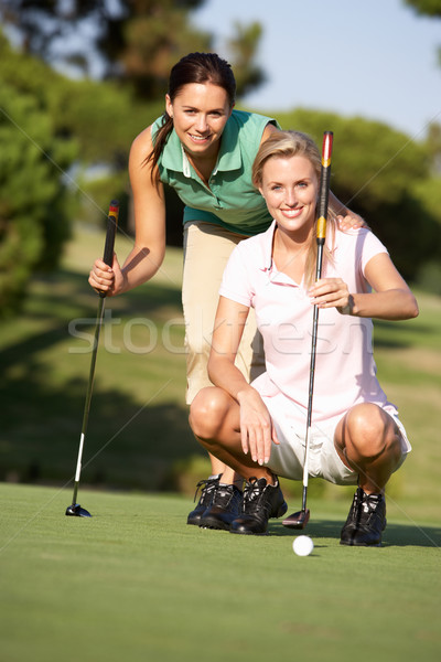 Two Female Golfers On Golf Course Lining Up Putt On Green Stock photo © monkey_business