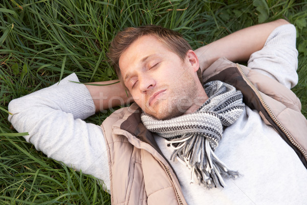 Young man napping alone on grass Stock photo © monkey_business