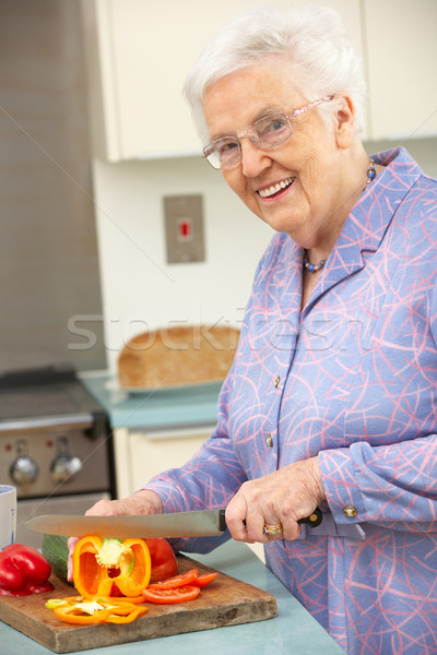 Senior woman chopping vegetables in domestic kitchen Stock photo © monkey_business
