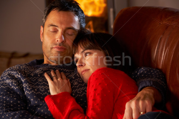 Middle Aged Couple Cuddling On Sofa By Cosy Log Fire Stock photo © monkey_business