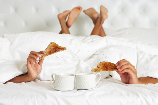 Couple Hiding Under Duvet Enjoying Breakfast In Bed Stock photo © monkey_business