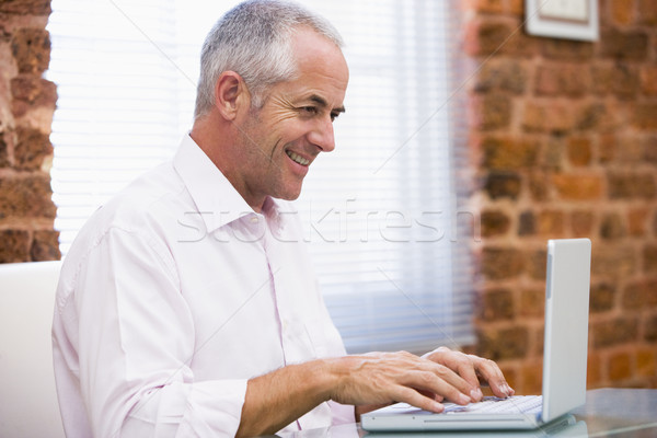 Businessman sitting in office typing on laptop smiling Stock photo © monkey_business