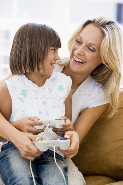 Woman and young girl in living room with video game controllers  Stock photo © monkey_business
