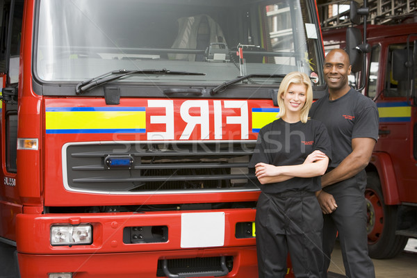Stock photo: Portrait of firefighters standing by a fire engine