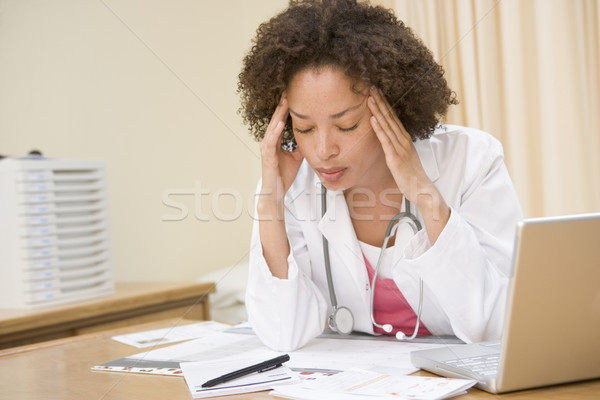 Doctor with laptop and headache in doctor's office Stock photo © monkey_business