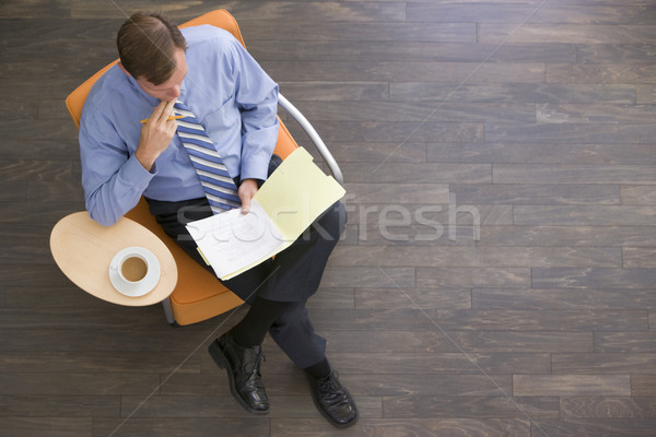 Businessman sitting indoors with coffee and folder Stock photo © monkey_business