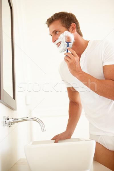 молодым человеком ванную зеркало улыбка человека портрет Сток-фото © monkey_business