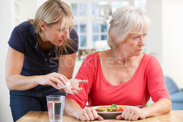 Idősebb nő gyógyszer otthon étel asztal Stock fotó © monkey_business