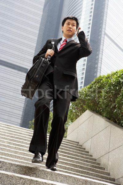 Chinese Businessman Rushing Down Steps On Mobile Phone Stock photo © monkey_business