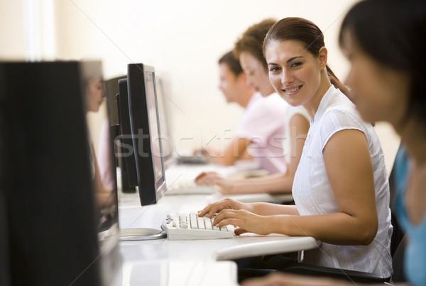 Cztery osoby posiedzenia sala komputerowa wpisując uśmiechnięty kobieta Zdjęcia stock © monkey_business