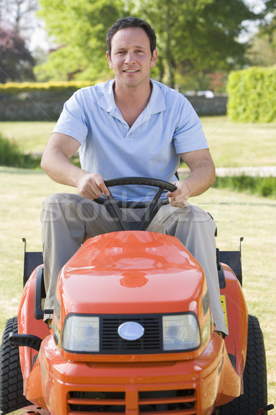 Man outdoors driving lawnmower smiling Stock photo © monkey_business