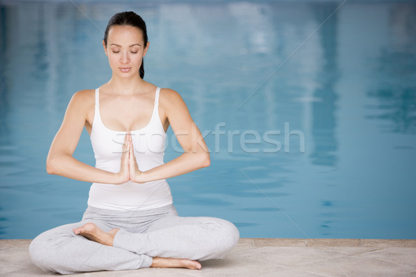 Woman sitting poolside doing yoga Stock photo © monkey_business