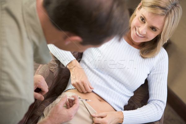 Stock photo: Man helping woman inject drugs to prepare for IVF treatment