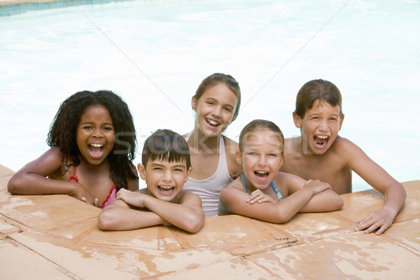 Five young friends in swimming pool smiling Stock photo © monkey_business