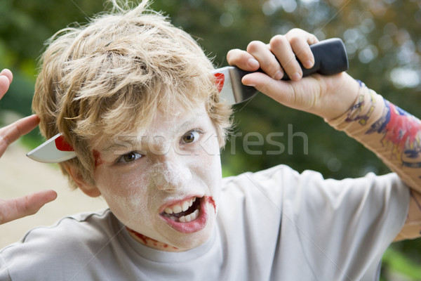 Stock photo: Young boy with scary Halloween make up and plastic knife through