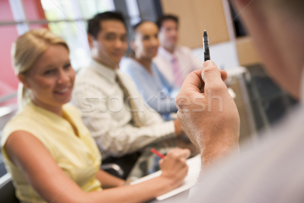 Five businesspeople at boardroom table with focus on businessman Stock photo © monkey_business