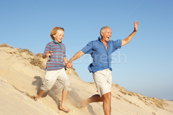 Grandfather And Grandson Enjoying Beach Holiday Running Down Dun Stock photo © monkey_business