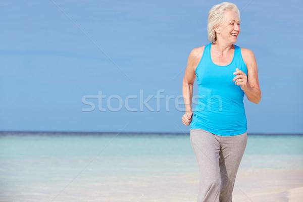 Senior Woman Running On Beautiful Beach Stock photo © monkey_business