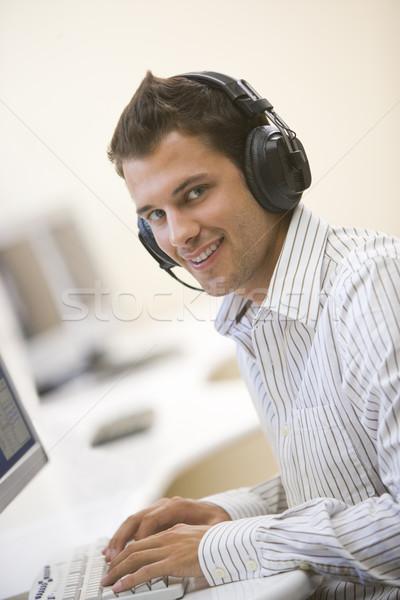 Man hoofdtelefoon computerruimte typen glimlachend Stockfoto © monkey_business