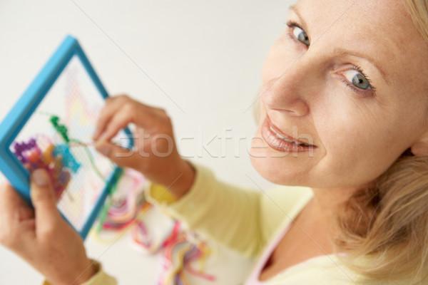 Mid age woman doing cross stitch Stock photo © monkey_business