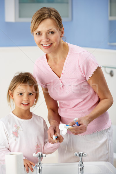 Mother and daughter cleaning teeth in bathroom Stock photo © monkey_business