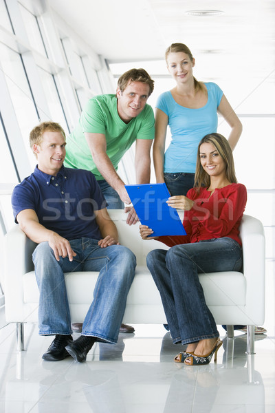 Zdjęcia stock: Cztery · osoby · lobby · wskazując · schowek · uśmiechnięty · zespołu