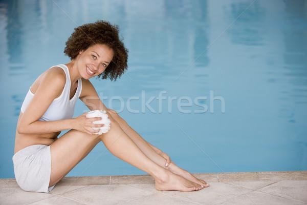 Woman sitting poolside using shower puff on leg smiling Stock photo © monkey_business