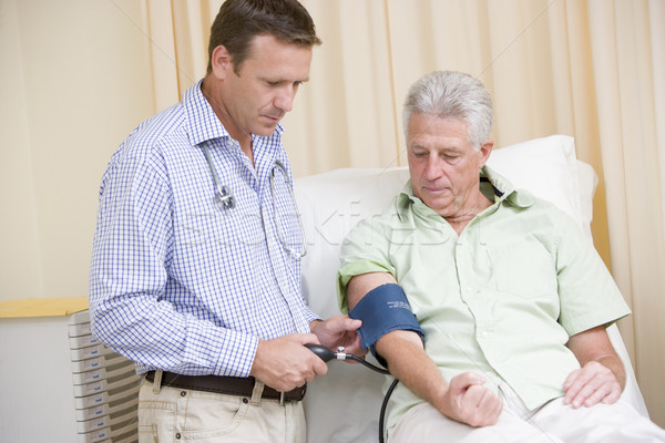 Doctor checking man's blood pressure in exam room Stock photo © monkey_business