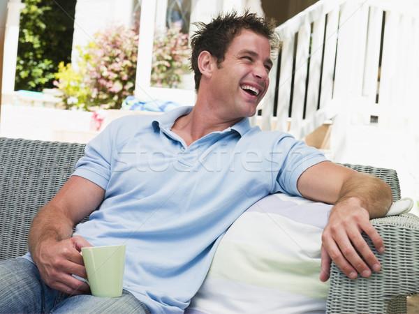 Stok fotoğraf: Adam · oturma · veranda · kahve · gülme · sandalye
