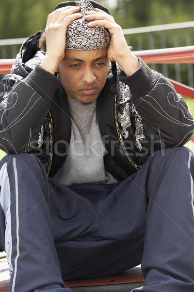 Jeune homme séance aire de jeux homme rue triste Photo stock © monkey_business