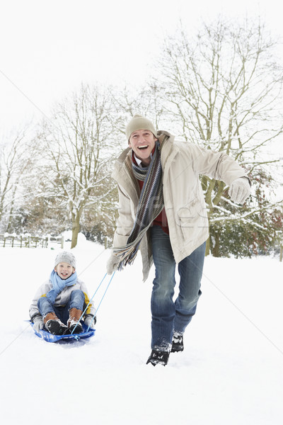 Father Pulling Son On Sledge Through Snowy Landscape Stock photo © monkey_business