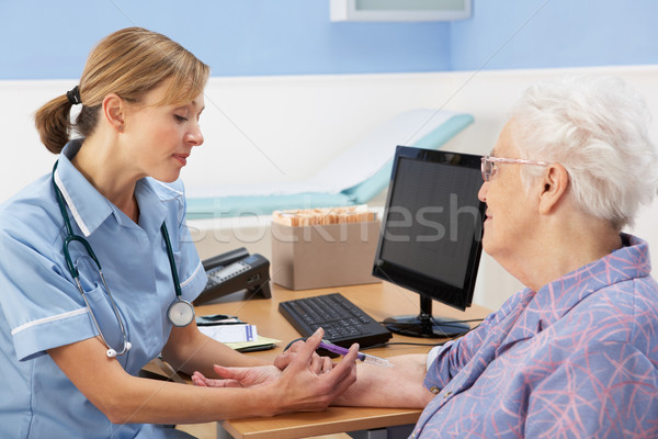 Stock photo: UK nurse injecting senior woman patient