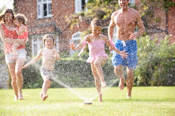 Family Running Through Garden Sprinkler Stock photo © monkey_business