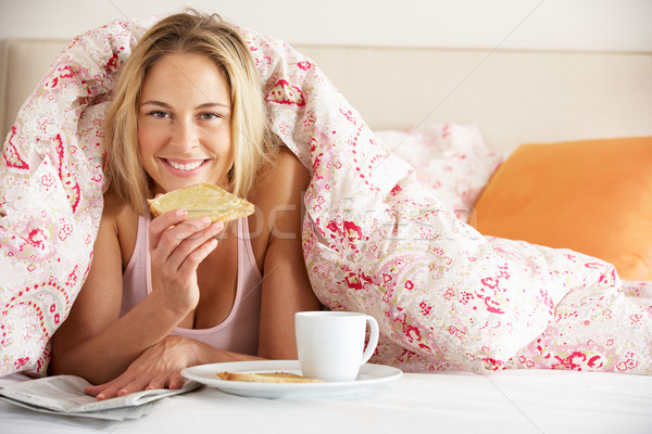 Pretty Woman Snuggled Under Duvet Eating Breakfast And Reading N Stock photo © monkey_business