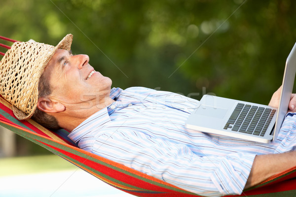 Senior Man Relaxing In Hammock With Laptop Stock photo © monkey_business