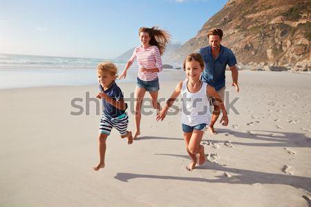 Family Walking Along Beach With Picnic Basket Stock photo © monkey_business