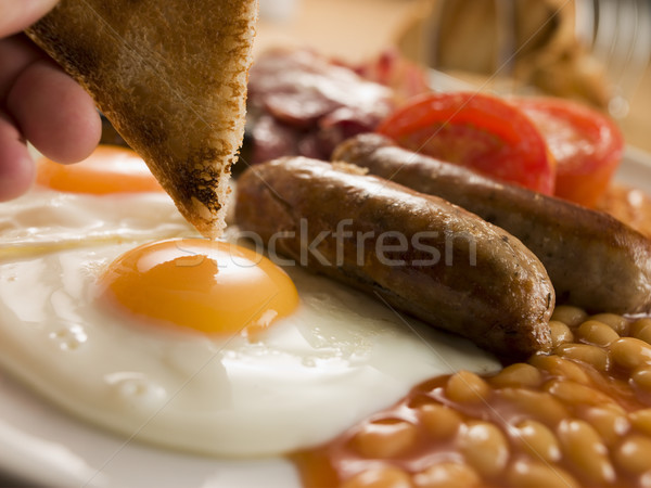 Dipping Toast into a Fried Egg on a Full English Breakfast Stock photo © monkey_business
