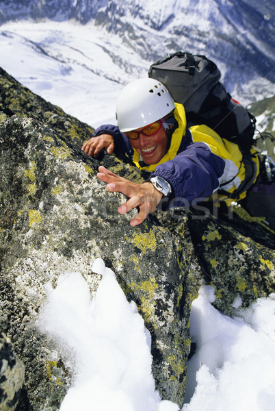Mountaineer climbing snowy rock face Stock photo © monkey_business