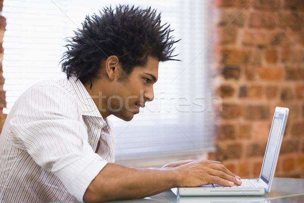 Stock photo: Businessman sitting in office typing on laptop