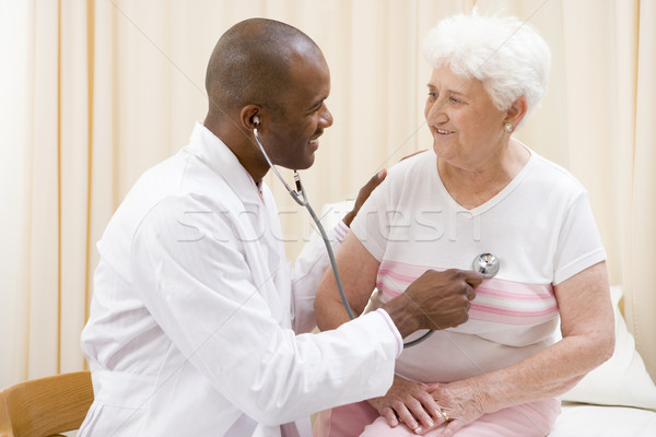 Doctor giving checkup with stethoscope to woman in exam room smi Stock photo © monkey_business