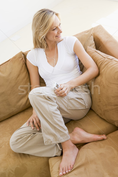 Woman in living room listening to MP3 player smiling Stock photo © monkey_business