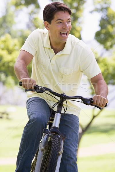 Man outdoors riding bike smiling Stock photo © monkey_business