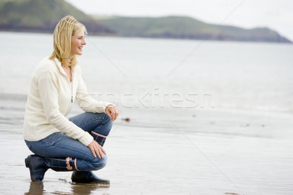 Woman crouching on beach smiling Stock photo © monkey_business