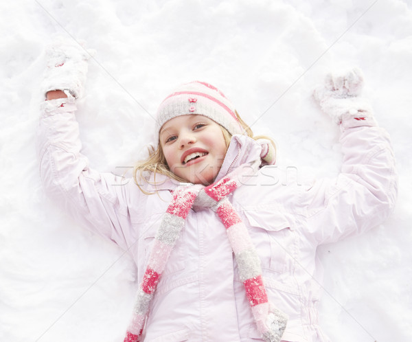 Girl Laying On Ground Making Snow Angel Stock photo © monkey_business