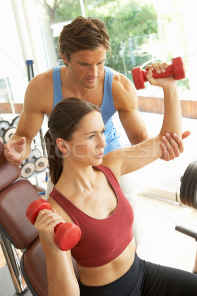 Young Woman Working With Weights In Gym With Personal Trainer Stock photo © monkey_business