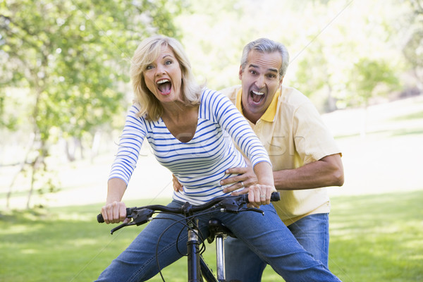 Couple on bike outdoors smiling and acting scared Stock photo © monkey_business