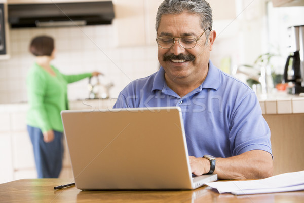 Man in kitchen with laptop smiling with woman in background Stock photo © monkey_business