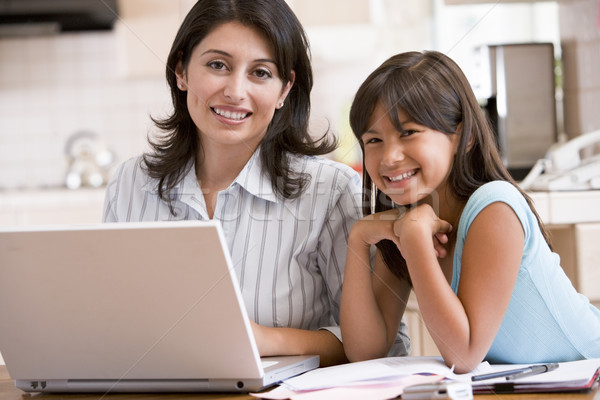 Woman and young girl in kitchen with laptop and paperwork smilin Stock photo © monkey_business